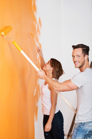 Portrait of loving couple painting wall of their new house photo