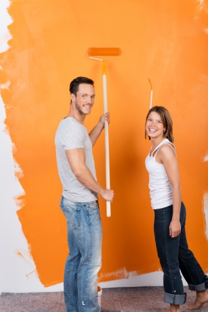 roller brush: Happy couple painting the interior of their new house Stock Photo