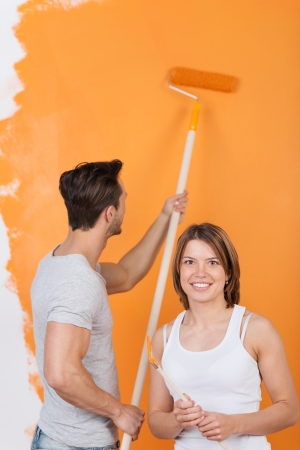 Young man is painting a wall and girlfriend smiles photo