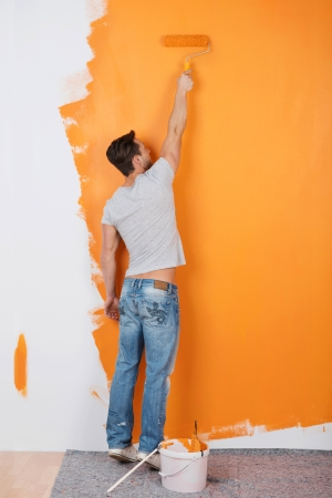 Man paints a wall with orange color Stock Photo - 21162108