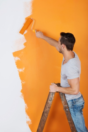 Young man is working with paint roller Stock Photo - 21162109