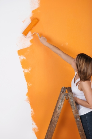 Young woman paints her appartment walls orange photo