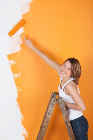 Sonriente ni�a est� pintando la pared de su ingenio de un rodillo photo