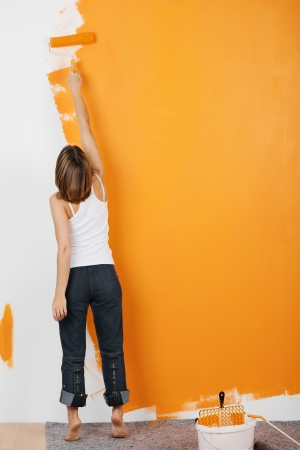 Young woman paints her walls orange with a roller photo