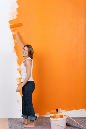 Girl is painting her appartment with orange color photo