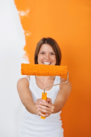 Smiling woman shows her paint roller covered in orange paint photo