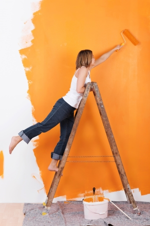 La mujer se coloca en una escalera para pintar su pared de color naranja photo