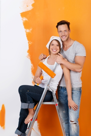 redecorating: Happy couple redecorating and painting with orange color