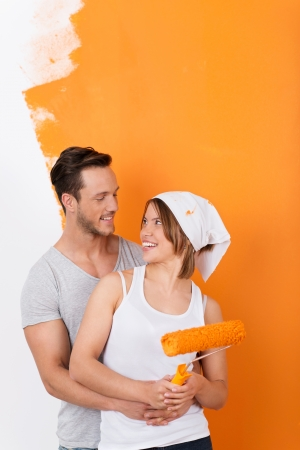 Happy young couple redoing their flat and painting walls photo