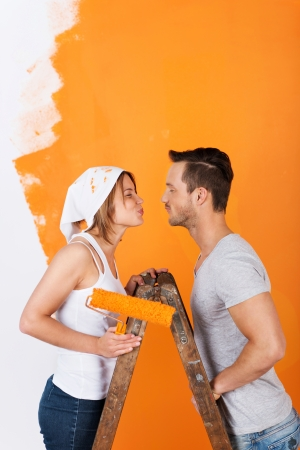 Couple kissing, while redecorating with orange paint Stock Photo