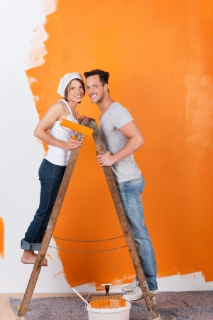 Young couple is standing on a ladder, while painting photo