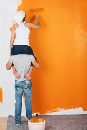 house renovation: Young couple is having fun painting a wall