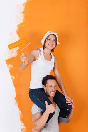 Man carries his girlfriend on his shoulders, while painting Stock Photo - 21156831