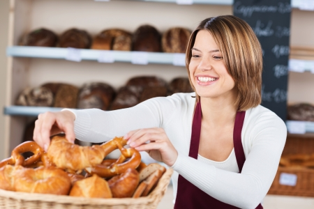 shops: Beautiful smiling woman in the bakery filling a basket with bread and cakes