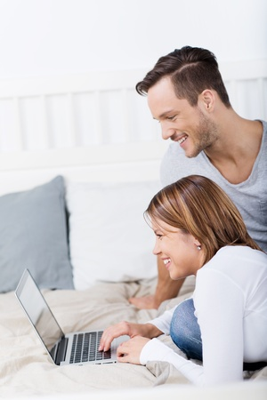 Couple comfortably in bed with a laptop photo