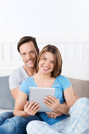 Couple in bed in pajamas with tablet photo