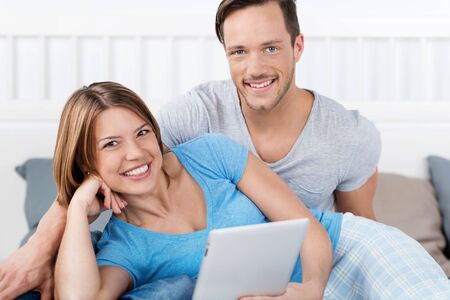 Happy couple in pajamas with tablet in bed photo