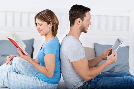 lying on back: Young couple is relaxing with a book and tablet in bed