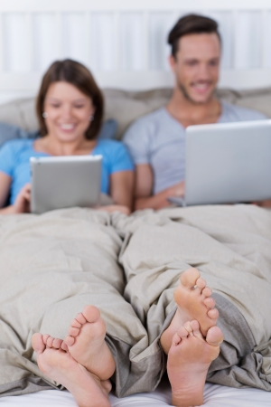 Couple in bed in pajamas with laptop photo