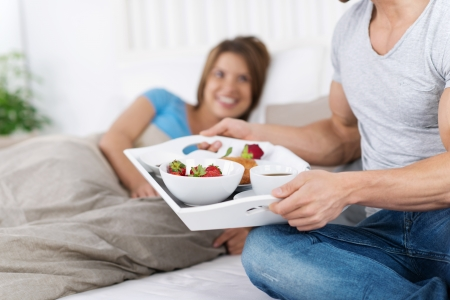 serving food: Man delivering breakfast on the tray to her spouse on bed in the morning