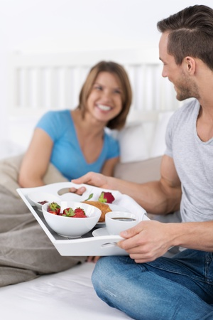 Loving Man delivering breakfast on the tray to her spouse on bed photo