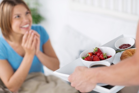 serving tray: Husband surprises her beautiful and happy wife with breakfast in bed bringing strawberries, a croissant and jam in a tray