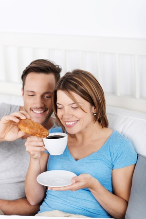 Attractive happy young couple sitting up against the pillows enjoying a delicious coffee and croissant in bed photo