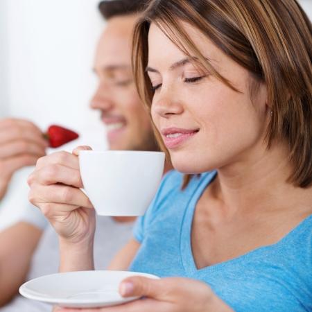 hombre tomando cafe: Mujer bonita que disfruta de una taza de café saboreando el aroma con los ojos cerrados en el placer Foto de archivo