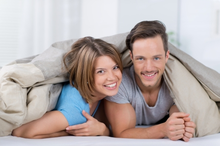 Cute romantic couple under a duvet in the bed Stock Photo - 21157220