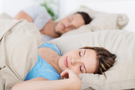 napping: Young couple sleeping in bed having a restful sleep, closeup of the wife Stock Photo