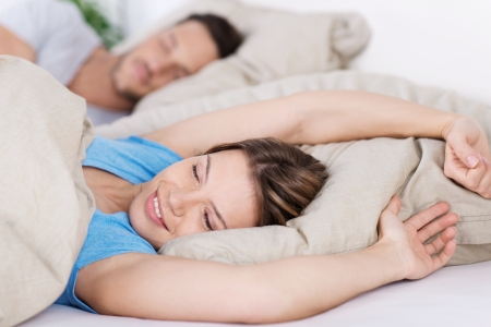 Young woman lying in bed awakening from a sleep stretching and smiling Stock Photo - 21162327