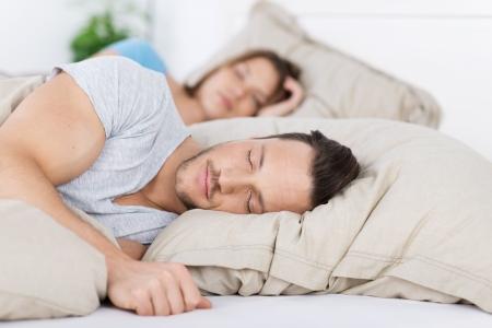couple sleeping: Joven pareja durmiendo juntos en la cama en su casa