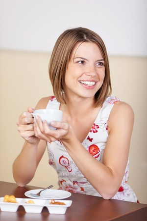 cradling: Young woman sitting in a cafe cradling a cup of coffee in her hands with her head turned smiling off to the right of the frame Stock Photo