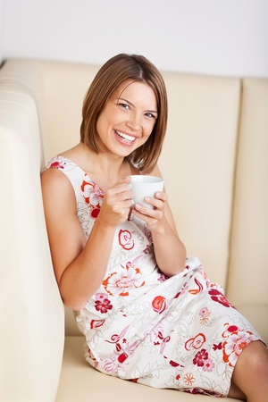 Laughing woman in a cafe relaxing on a comfortable bench with a cup of coffee in her hands Stock Photo - 21162355