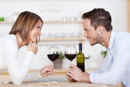 Happy couple enjoys a glass of red wine