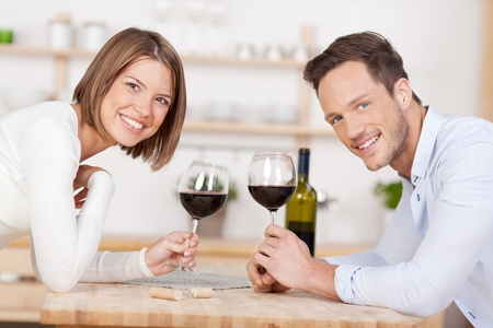 Smiling couple drink a glass of red wine photo