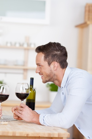 Smiling young man toasts with a glass of red wine photo