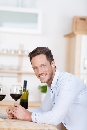 Smiling young man enjoying a glass of red wine leaning on a kitchen counter photo