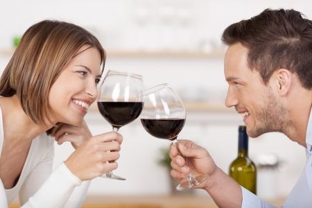 dating couples: Happy couple toasting with red wine leaning towards each other smiling as they celebrate