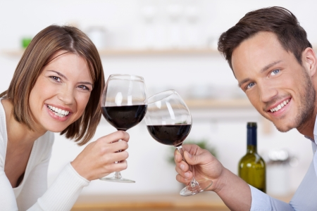 Smiling couple with glasses of red wine clinking their glasses in a toast and looking at the camera photo