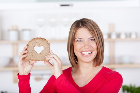 Smiling beautiful woman holding a bread slice with a hearth shape carved in the middle photo