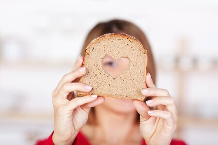 obscured face: Slice of whole grain bread with a heart