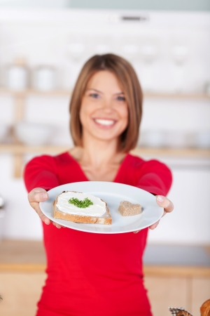 Slice of bread with cream cheese and cress shown by young woman photo