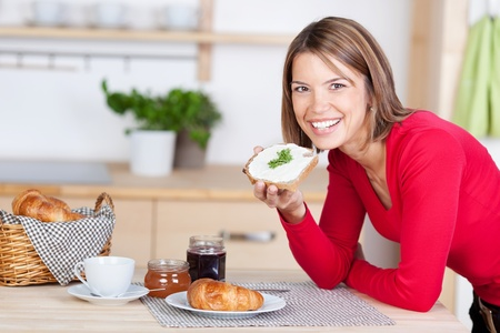 Smiling girl saviours her breakfast at home photo