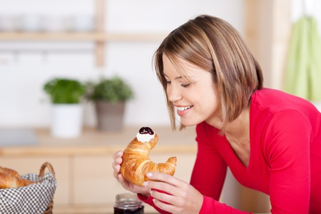 Woman having a freshly baked croissant for breakfast looking at it with anticipation as she prepares to take a mouthful photo