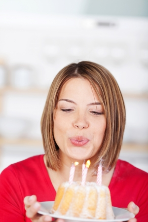 Woman blowing out her birthday candles holding a small glazed ring cake on a plate in front of her photo