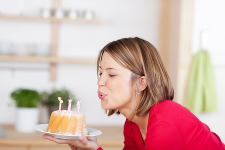 Young woman blowing out her birthday candles leaning forwards with the cake in her hands, indoor head and shoulders profile portrait