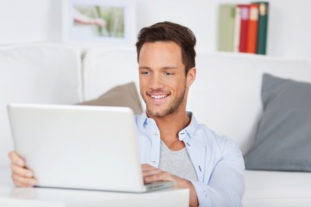 Handsome man browsing the internet in the living room Stock Photo - 21162432