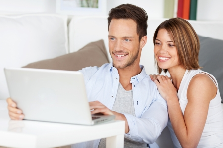 guy with laptop: Beautiful couple sitting on the floor with laptop in the living room Stock Photo