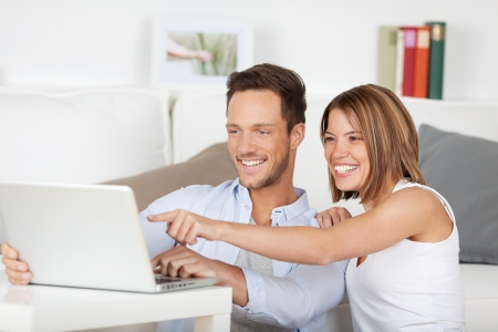 woman searching: Laughing couple browsing through laptop on the table